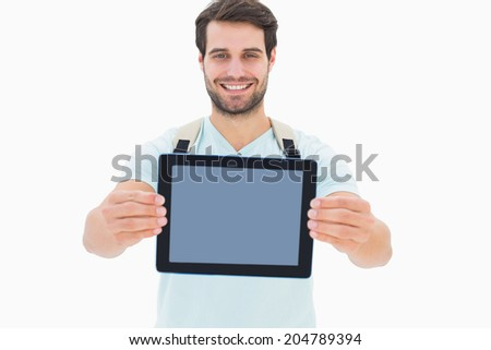 Handsome student showing his tablet pc on white background - stock photo