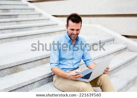 Handsome student sitting on stone steps and using a laptop and mobile - stock photo