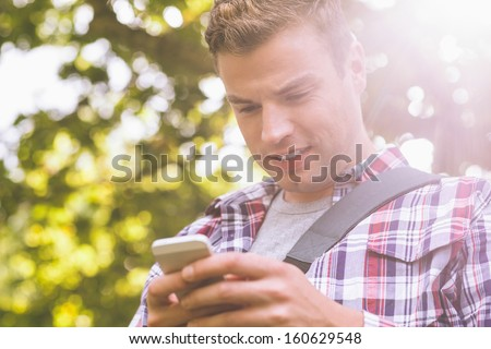 Handsome student standing and texting on campus at college - stock photo