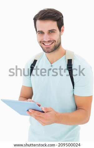 Handsome student using his tablet pc on white background