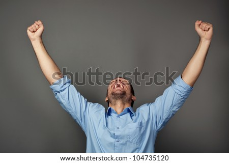Handsome student with raised arms screaming - stock photo
