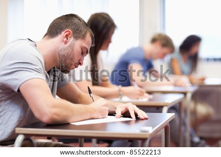Handsome student writing an assignment in a classroom - stock photo