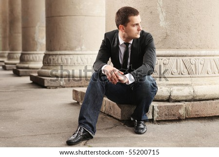 handsome stylish businessman sitting near column - stock photo