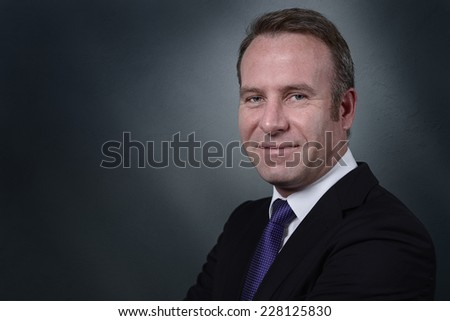 Handsome stylish businessman with an attentive expression looking directly at the camera, on a grey background with copy space