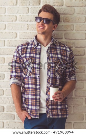 Handsome stylish guy in casual shirt and sun glasses is holding a cup of coffee and smiling, on a white brick wall background