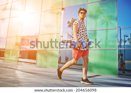 Handsome stylish guy walking with long-board in the hands, urban culture - stock photo