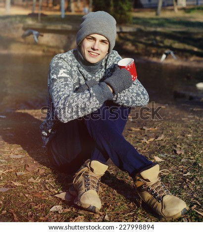 Handsome stylish happy young man in the sweater and hat with the cup of tea or coffee in the autumn park near water