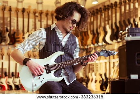 Handsome stylish man in classical vest and sunglasses smiling while playing an electric ain a musical shop