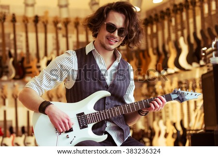 Handsome stylish man in classical vest and sunglasses smiling while playing an electric guitar in a musical shop - stock photo