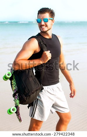 Handsome stylish man in hipster shirt and sunglasses posing near sea side at sunshine, enjoying beautiful view and relax near ocean.Surfer man at  wetsuit,surf fan,tan,obsession,surf on bali - stock photo