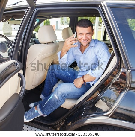 Handsome stylish man on a back seat with a mobile phone