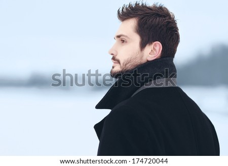 Handsome stylish man outdoors with a thoughtful look into the distance in winter field - stock photo