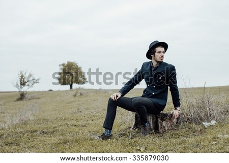 handsome stylish man posing on a green field with cool clothes