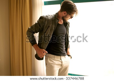 Handsome stylish man posing outdoor at hotel near the window,young travel businessman waiting for his lunch at hotel room,successful male on his 30th,man,leather black jacket,male fashion,cozy clothes - stock photo