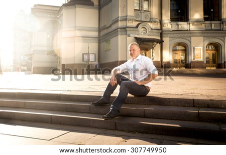Handsome stylish man relaxing on stone stairs at big classic building - stock photo