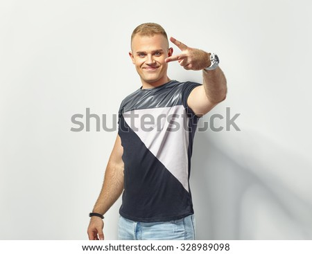 Handsome stylish man showing victory sign - stock photo