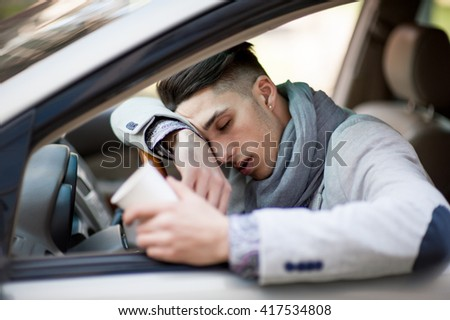 Handsome stylish man sleeps in car feels dangerous