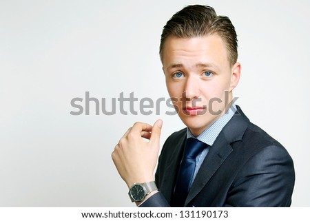 Handsome stylish young businessman with a look of puzzlement looking at the camera with his hand raised   head and shoulders studio portrait on white
