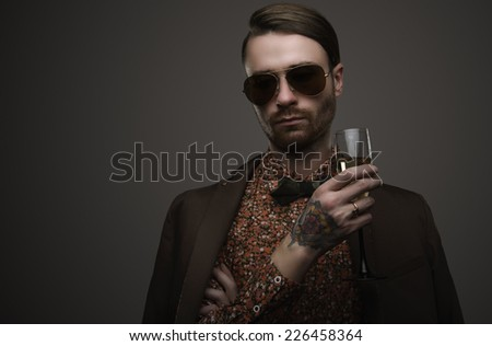 Handsome stylish young man. Brutal man with a beard and sunglasses. Man with champagne