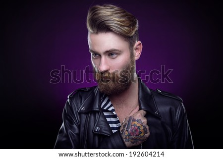 Handsome stylish young man. Brutal man with a beard and tattoo - stock photo