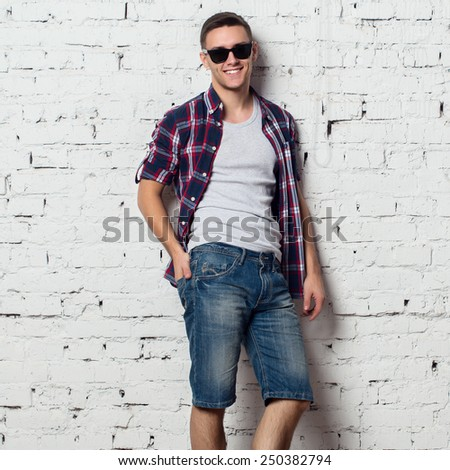 Handsome stylish young man in jeans shorts and shirt. Attractive hipster  with a bristle,sunglasses. - stock photo