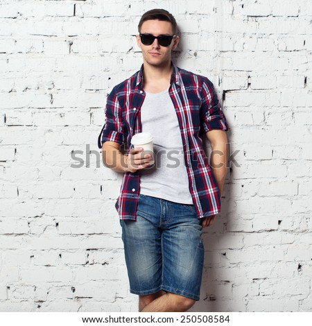 Handsome stylish young man in jeans shorts and shirt. Brutal man with a bristle, sunglasses and coffee. brick wall. - stock photo