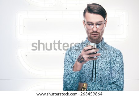 Handsome stylish young man in shirt looking to the phone. Man In Use the Internet via the phone. Mobile Technologies - stock photo