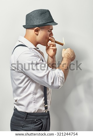Handsome stylish young man smoking cigar - stock photo