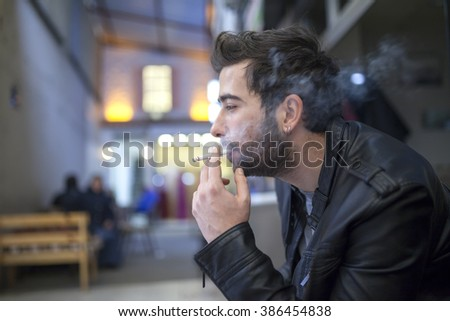 Handsome stylish young man smoking outside - stock photo