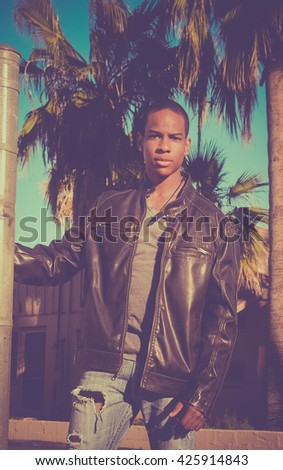 Handsome stylish young man wearing leather jacket - sunny day palm tree background.