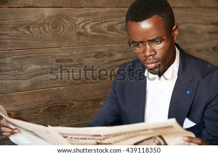 Handsome successful African corporate worker with stylish mustache, wearing glasses, reading news in paper with concentrated look during lunchtime, looking fashionable in his dark blue suit - stock photo