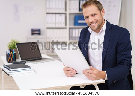 Handsome successful businessman working at a table in the office holding an online document on a tablet in his hands and smiling at the camera