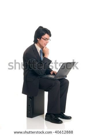 Handsome successful young businessman with briefcase and laptop, joyful expression, studio shot. - stock photo