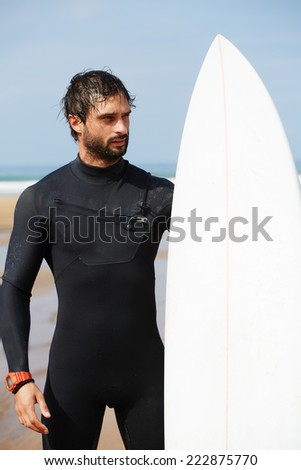 Handsome surfer man in black diving suit holding his surfboard, young professional surfer dressed in black wetsuit looking along the shore for find the perfect spot with big waves for surfing - stock photo