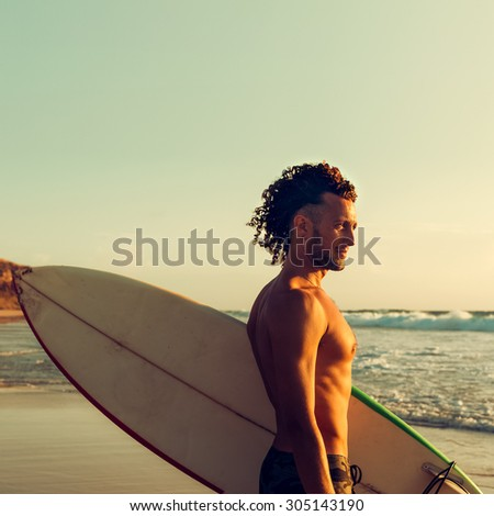 Handsome Surfer on the Beach at Sunset - stock photo