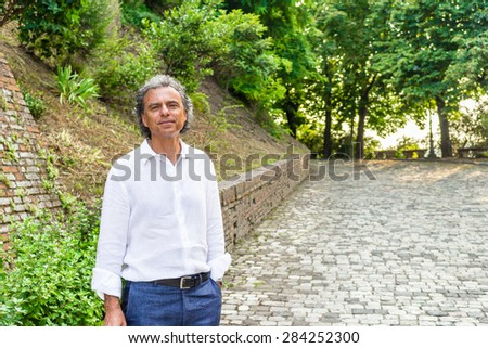 Handsome tanned middle-aged man with salt pepper hair and green eyes dressed with linen white shirt and blue pants in Italian medieval outdoors: he is relaxed near brick walls of a medieval building - stock photo