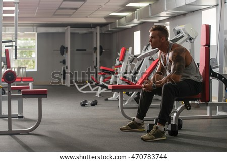 Handsome tattooed bodybuilder posing in gym