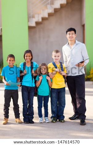 handsome teacher and elementary school students on campus - stock photo