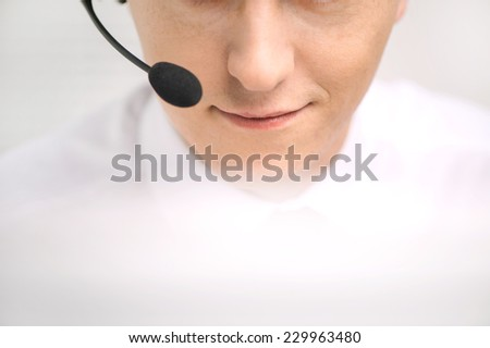 handsome technical support operator working on computer. male mouth with headset portrait at bright call center helpdesk support office  - stock photo