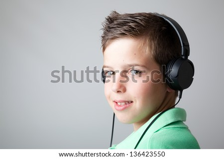 Handsome teen boy listening to music on headphones over grey background - stock photo