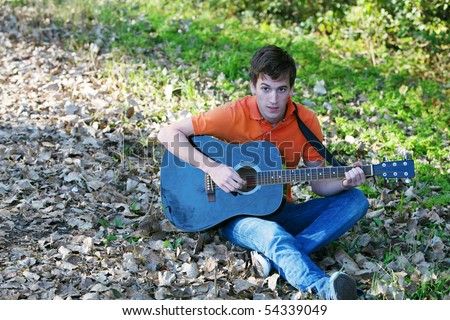 handsome teen boy sitting outside playing guitar