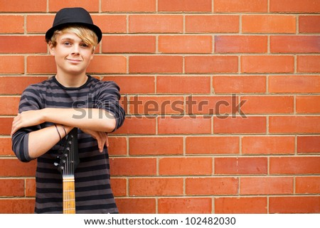 handsome teen boy with guitar outdoors - stock photo