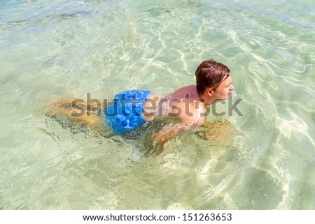 handsome teen has fun swimming in the ocean