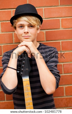handsome teen musician portrait with guitar - stock photo