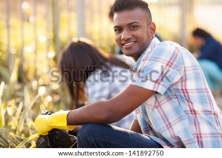handsome teen volunteer cleaning streets with friends - stock photo