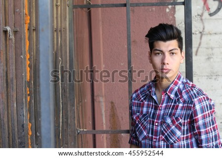 Handsome teenage boy in plaid posing on edgy cool background with copy space for text message - stock photo