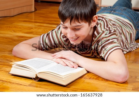 Handsome teenage boy reading book while lying on the parquet. - stock photo