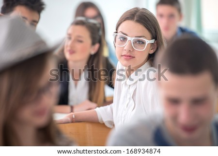 Handsome teenage girl with glasses sitting in classroom - stock photo