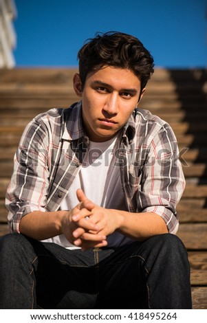 Handsome teenager outdoors, sitting on steps, thinking - stock photo