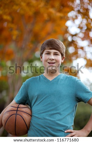 Handsome Teenager with Basketball on an Autumn day - stock photo